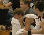 Lansing High junior Cody Mohan watches the game from the bench with an ice pack on his left shoulder. Mohan, the Lions' starting point guard, injured the shoulder in a car accident before the game.