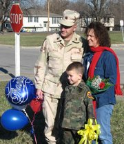 Maj. Richard DaSilva poses with his wife, Jeannie, and son, Jonah, in front of Lansing Elementary School. Jonah, a first-grader at the school, is holding a yellow ribbon that had hung outside the school while his father was serving in Iraq. When DaSilva came home and visited the school Friday, he and Jonah cut down the ribbon