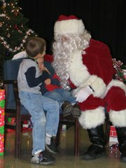 Alex White, 5, and his brother Mykael, 2, tell Santa what they want for Christmas at the Lansing Parents and Teachers Association's Breakfast with Santa on Saturday.