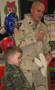 Army reserve Maj. Richard DaSilva, right, shows first-graders at Lansing Elementary School how Iraqis express thanks.
