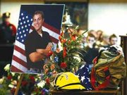 The hat and uniform of volunteer firefighter Jared Moore stood in the center of the memorial service Monday at Savior of the World in Kansas City, Kans.