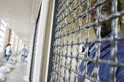 Inmate Nathaniel Carroll peers out from inside his cell in the maximum security D-cell at the Lansing Correctional Facility.  Carroll draws portraits to pass the time while locked up.