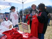 "Keasla Hundley, left, shows off a ""Vote for Kids"" T-shirt to Yvonne Willcott and Teana Hundley at the ""Bond Fire,"" sponsored by the Vote for Kids committee. The fire was Sunday at teh site of the proposed new Lansing Elementary School."