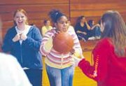 Seventh-graders Lauren Roberts, left, and Britainee Baker circle up to play a game for Hoops for Heart in the Lexington Trails Middle School gym.