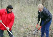 Janice Downey, left, and Lorraine Gluch, right - both members of the 2005 Lansing-Leavenworth Leadership class - cleared new trial space at Kelly Grove Park.