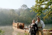 Lynette Trotter and Bill Stewart are photographed in period costume at Big Bone Lake State Park, Ky., near a replica of the keelboat Lewis and Clark used to explore the American Plains and Northwest.