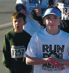 Flanked by Starside Elementary School students, running club sponsor Amanda Wilkins helps keep pace for the club during a 5K race Saturday in Shawnee. About 30 students participate regularly in the running club.