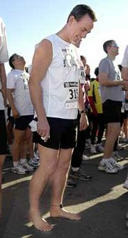 Wearing no running shoes, Rick Roeber checks his feet before the start of the Run for Mercy benefit race.