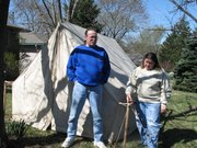 Lynette Trotter and Bill Stewart stand in front of a tent outside their Lansing home.