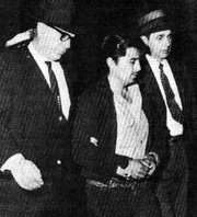 In 1959, Kansas Bureau of Investigation agents Clarence Duntz, left, and Al Dewey, right, bring Perry Smith to court.