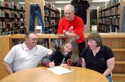 Jessica Kane, center, signs her letter-of-intent to play softball at Kansas City Kansas Community College. The senior pitcher was joined by her parents, Rob and Nancy Kane, sitting, and Lansing High coach Terry Cornett.