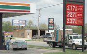 A customer fuels his car at the 7-Eleven store on Main Street. Gasoline is down in price from earlier this month, but it still costs about 41 cents a gallon more than it did last year at this time.