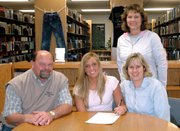 Lansing High senior Emily Goodlin, center, was joined by her parents, Jeff and Chris Goodlin, and LHS volleyball coach Julie Slater when Goodlin signed her letter-of-intent Tuesday to play volleyball at JCCC.