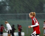 LHS senior Kelsey Fallesen races up the field while being pounded by a heavy downpour Monday at Olathe Northwest.
