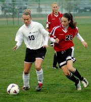 LHS freshman Rachel Pride battles an Olathe Northwest player for the ball during the Lions' 3-0 loss Monday.