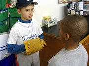 Drew Poirier, left, representing baseball player Jackie Robinson, tells Andrew Tremain about Robinson's life and achievements Thursday at LIS.