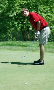 Senior Chris Nelson eyes his putt at the Kaw Valley League meet.