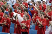 Students from Lansing Intermediate School wear matching red shirts and clap along to music Thursday at the D.A.R.E. concert at Verizon Amphitheater. The program included music from local law enforcement musicians and a visit from Retro Bill, spokesman for the D.A.R.E. program.