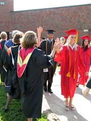 Seniors receive congratulatory high-fives from faculty members.