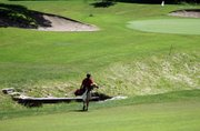 Chris Nelson makes the long walk toward a green at the state golf tournament at Ironhorse Golf Club.