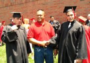 Lansing Educational Achievement Program graduates Grant, left, and Gavin Maiava received a unique graduation gift: Their father, Tony Maiava, center, returned home from Iraq where he is serving.