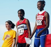 Freshman Takeisha Jenkins celebrated on the medal stand after placing second at state in the 300-meter hurdles.
