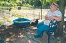 Carol Wooten keeps company with two hens while her husband, Lyle, mulches the couple's vegetable garden. The Wootens allow visitors, expected and unexpected, to browse the garden and iris beds they've cultivated behind their home near Mize Road.