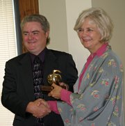 Dan Wiley, president of the Leavenworth-Lansing Area Chamber of Commerce, left, presents a Golden Apple Award for teaching excellence to Cathy Smith, of Lansing Intermediate School. Smith was one of three teachers honored Saturday.