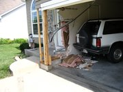 Two-by-fours, above, brace the corner of the garage at 705 Holiday Drive, the home of James and Lynn Driscoll. Authorities have charged a Leavenworth man, Thomas Brooks, 26, with ramming the house with his pickup while driving under the influence. The incident occurred Friday night.