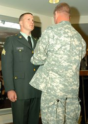 Sgt. Maj. of the Army Kenneth Preston, right, pins the Combat Action Badge on Sgt. Timothy Gustafson during a June 29 ceremony at the Pentagon.