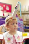 One-year-old Sara Murphy peers out from beneath a unicorn horn she