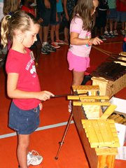"First-graders Emma Bresser, left, and Emily Arwine, play xylophones during rehearsal of the song ""Rhythm of the Rain."" The girls participated in Lansing PTA Music and Art camp at Lansing Elementary School this week."