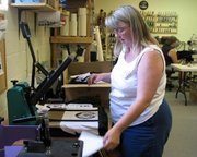 Celia Hansen, owner of Ceal's Designs and Signs, 110 S. Main St., removes a transfer sheet from a completed canvas bag, one of many being made for the Command and General Staff College at Fort Leavenworth. Hansen is using an in-house custom heat press with transfers that Ceal's Designs and Signs orders from St. Joseph, Mo., to screenprint the design onto the bags.