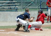 Lansing Cavalry catcher Lonnie Hansen tags out a Blue Valley West runner at the plate during the Zone Tournament.