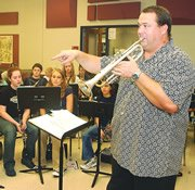 LTMS instrumental music teacher Robert Foster plays along while signaling directions to the middle school band's trumpet section. The hiring of Foster allowed changes in how instrumental music is taught at the middle school and De Soto High School.