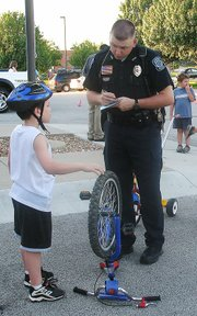 Lansing Police Officer Michael Heuer registers the bicycle of Brian Orkwis, 8, Lansing, at Monday's bike rodeo. Officers and Scout leaders also taught bike-riding safety.