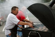 Rob Kane flips burgers for the Lansing Booster Club before Lansing High's season opener against Tonganoxie. Kane, a lineman with Westar Energy, has cooked burgers before LHS football games for four years, but he missed last week because he was headed to New Orleans to aid in Hurricane Katrina relief efforts.