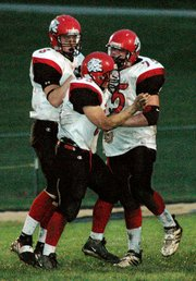 Ryan Robbins and Logan Ryan celebrate with Jason Bowman after Bowman sacked Bonner Springs' quarterback.