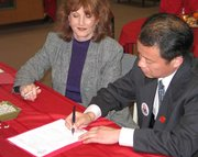 Kaifeng principal Wang Kai signs an agreement for a student exchange program between Lansing High School and Kaifeng No. 5 Middle School. Lansing assistant schools superintendent Donna Hughes, left, also signed the agreement to seal the deal.