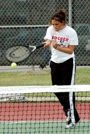 Lansing senior Lindsay Parks fires a return during a doubles match at the Gardner Invitational.