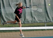 Lansing High junior Kersten Probst smashes a return during her first-round match at the Class 5A regional tournament.