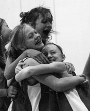Seventh-graders Heather Averill, left, Sarra Garvey, center, and Taylor Williams hug after beating Tonganoxie on Oct. 3 at LMS.