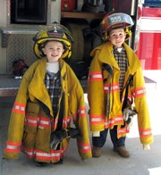Alex Tucker, 4, left, and Ezra Lanaman, 5, don firefighter coats during the open house at the High Prairie Township fire station.