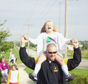 A skinned knee doesn't bother second-grader Annie Schmucker as she rides on the shoulders of John Zvirgzdins. The group walked around Starside Elementary School, the De Soto district offices and De Soto High School to kick off an awareness campaign for good health.