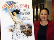 """Hollie Becker, project coordinator for """"The World War I Years: America Becomes a World Power,"""" stands next to a poster from the war years. The discussion and film series continues at University of Saint Mary."""