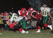 Senior Logan Ryan tackles a Basehor running back for a loss as teammates Ryan Robbins and Lance Fink assist.