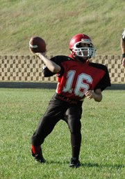 Lansing Middle School seventh-grade quarterback Tyler Terron fires a pass toward the end zone during the Lions' 32-8 victory over Tonganoxie on Tuesday afternoon at LMS.