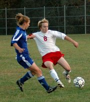 Lansing High senior midfielder Mike Bayless battles with Perry-Lecompton's Emily Kuenzi for control of the ball.
