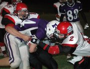 Joe Kohl and Kyle Grape wrap up Piper receiver Jimmy Burgess.