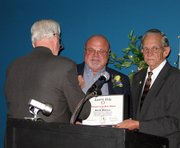 While receiving a pin from Gene Young, left, Dale Bohannon shows off the certificate designating him the Lansing PRIDE Volunteer of the Year for 2005. Mayor Kenneth Bernard, right, introduced Bohannon as the award winner during the annual Recognition Dinner on Monday at the Lansing Community Center.
